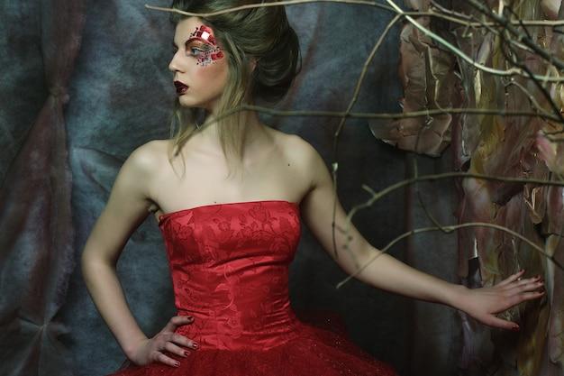 髪型、赤い唇、アートドレスとロマンチックな美しい少女のファッションの肖像画。ミステリーハウスのプリンセス。クリエイティブなコンセプト昔々ファンタジーで。