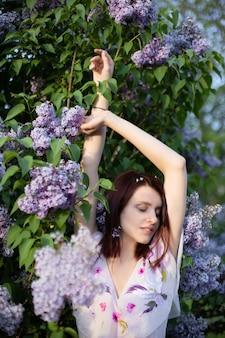 Модный портрет романтичной девушки, поднимающей руки возле цветущего куста сирени, весеннее настроение