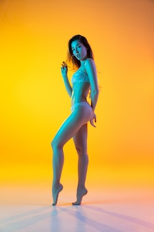 Модный портрет соблазнительной девушки в стильных купальниках на желтом фоне в неоне