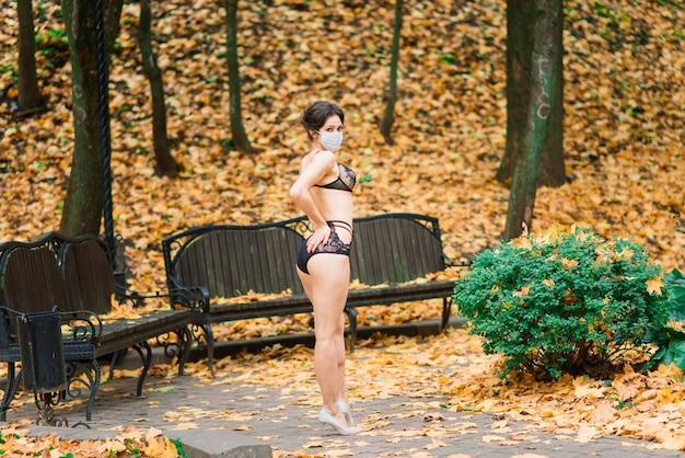 얼굴 마스크에 섹시 한 여자와 가을 공원에서 바디 슈트의 패션 초상화. 유행성, 바이러스, 코로나 바이러스