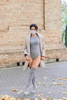 秋の公園でフェイスマスクとボディースーツのセクシーな女性のファッションの肖像画。パンデミック、ウイルス、コロナウイルス