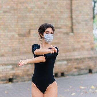 Фасонируйте портрет сексуальной женщины в лицевой маске и боди в осеннем парке. пандемия, вирус, коронавирус
