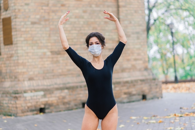 Фасонируйте портрет сексуальной женщины в лицевой маске и нижнем белье в осеннем парке. пандемия, вирус, коронавирус