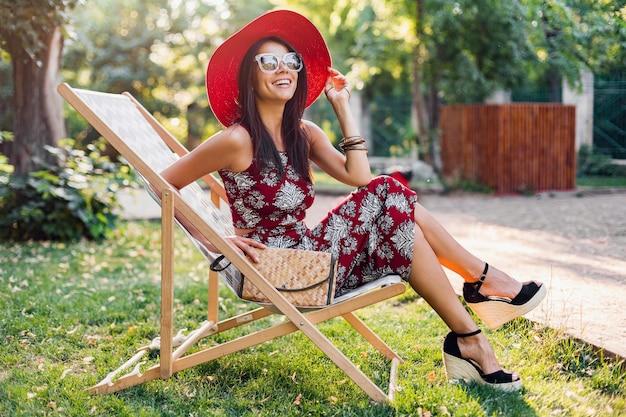夏服のプリントドレスでポーズをとって、流行のアクセサリー、財布、サングラス、赤い帽子を身に着けて、デッキチェアで休暇でリラックスして笑顔の魅力的なスタイリッシュな女性のファッションの肖像画