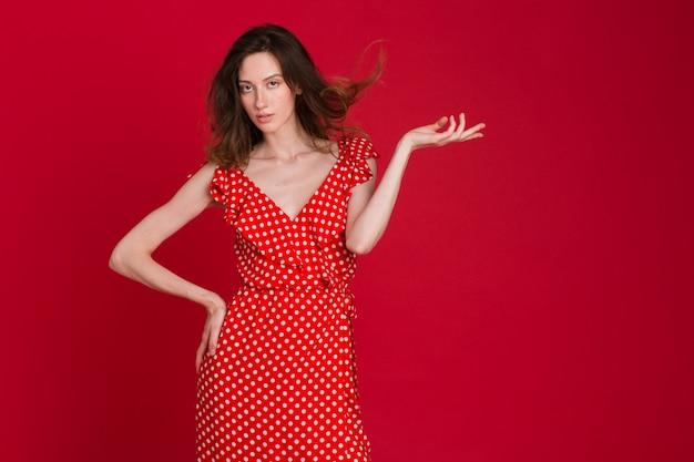 Модный портрет улыбающейся молодой женщины в красном платье в горошек на красном