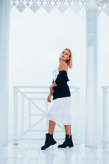 海の景色を望む豪華な場所でシルクのロングドレス黒のブレザーと大きなブーツでスタイリッシュな白人女性のファッションの肖像画