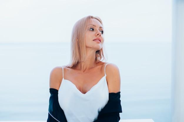海の景色を望む豪華な場所でシルクのロングドレス黒ブレザーのスタイリッシュな白人女性のファッションの肖像画