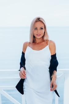 바다 전망과 고급스러운 장소에서 실크 긴 드레스 검은 재킷에 세련된 백인 여자의 패션 초상화