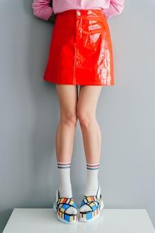 おしゃれな靴と赤いスカートでスタイリッシュな女の子のファッションの肖像画