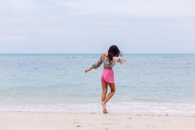 Модный портрет стильной женщины в красочной печати с длинным рукавом и розовых шортах на пляже, тропическом фоне.
