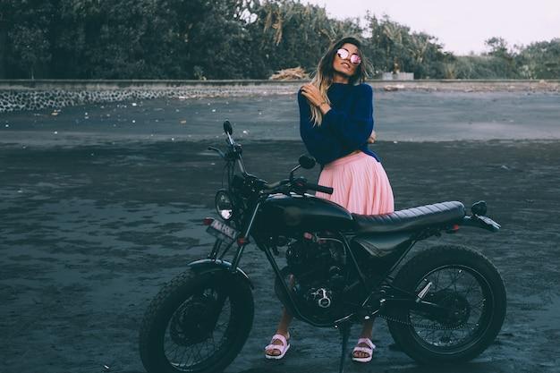 サングラス、青いセーター、ピンクのスカートのスタイリッシュな女性のファッションの肖像画は、黒い砂のビーチで黒い自転車のそばに立っています。