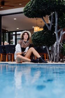 클래식 모자 블랙 바디 슈트에 세련된 여성 전문 모델의 패션 초상화