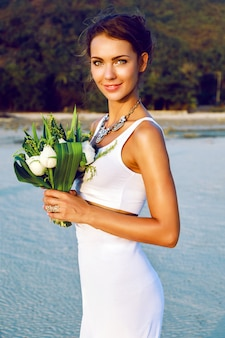 ビーチで素晴らしいエキゾチックな白い蓮の花束でポーズをとってシンプルなモダンなウェディングドレスで優しいスタイリッシュな花嫁のファッションの肖像画。黄金色の日差し。