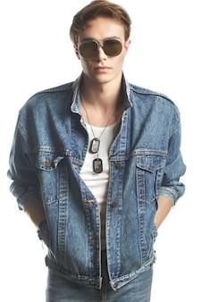 白で隔離のジーンズジャケットを着ている若いハンサムな男のファッションの肖像画
