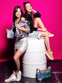 여름에 두 웃는 갈색 머리 모델의 패션 초상화, 흰색 배럴에 앉아 분홍색에 포즈 캐주얼 힙 스터 옷