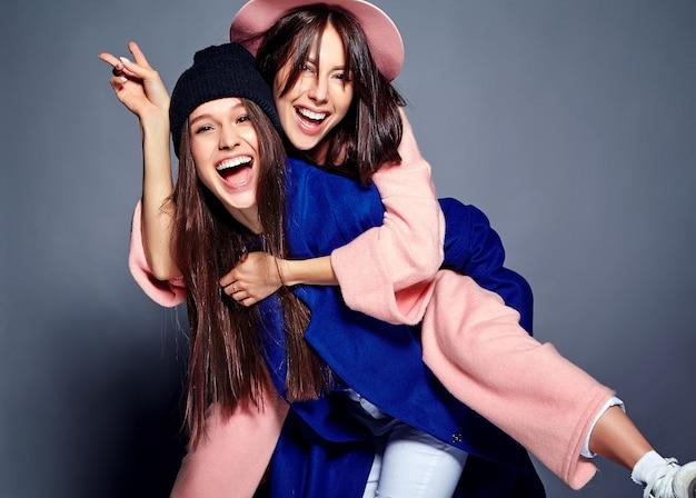 夏のカジュアルな流行に敏感なオーバーコートポーズで2つの笑顔ブルネットの女性モデルのファッションの肖像画。背中にお互いを保持している女の子