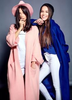 Мода портрет двух улыбающихся женщин брюнетка модели в летнее время случайные пальто битник позирует на серый