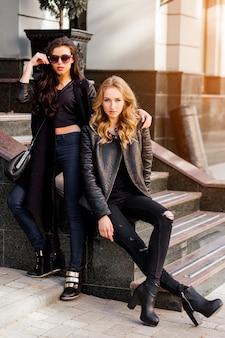 Фасонируйте портрет двух стильных симпатичных женщин, позирующих на улице в солнечный день. носит модный городской образ, кожаную куртку и сапоги на каблуке. молодые друзья ждут на открытой лестнице.