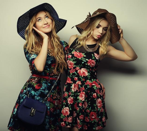 Фасонируйте портрет двух лучших друзей стильных сексуальных девушек, одетых в платье и шляпы. счастливое время для удовольствия.