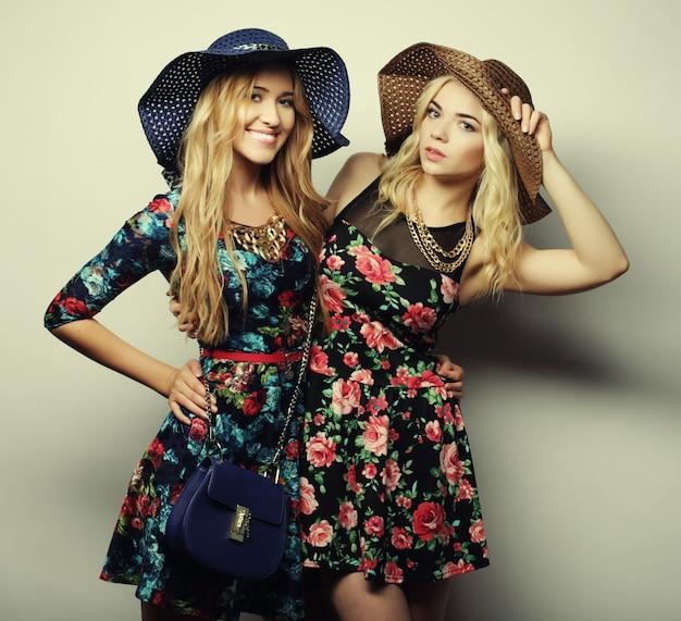 ドレスと帽子を身に着けている2人のスタイリッシュなセクシーな女の子の親友のファッションの肖像画。楽しみのための幸せな時間。