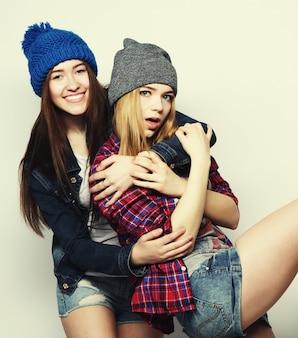 かわいい盗品の衣装と帽子を身に着けている、2人のスタイリッシュでセクシーなヒップスターの女の子の親友のファッションの肖像画。灰色の背景の上。