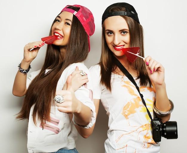 밝은 화장을 하고 사탕을 들고 있는 두 젊은 힙스터 소녀의 패션 초상화. 재미 있고 재미있는 얼굴을 만드는 두 명의 쾌활한 가장 친한 친구 자매의 스튜디오 초상화.