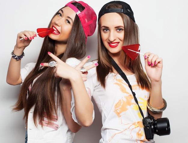 明るいメイクをしてキャンディーを持っている2人の若いかわいいヒップスターの女の子のファッションの肖像画。楽しんで変な顔をしている2人の陽気な親友の姉妹のスタジオポートレート。