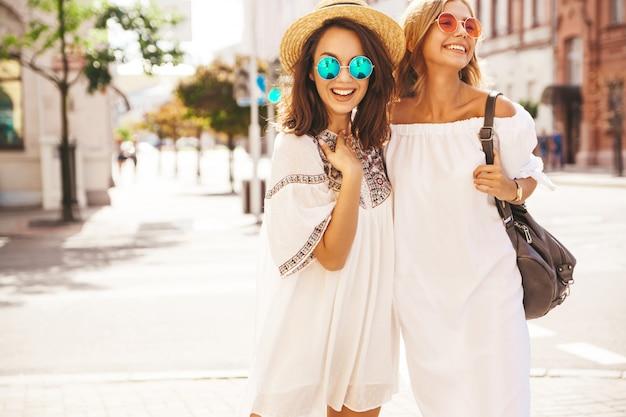 Фасонируйте портрет 2 молодых стильных моделей брюнетки и белокурых женщин хиппи в солнечный летний день в белый представлять одежд битника. схожу с ума