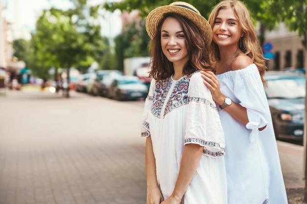 Фасонируйте портрет 2 молодых стильных моделей брюнетки и белокурых женщин хиппи в солнечный летний день в белый представлять одежд битника. без макияжа
