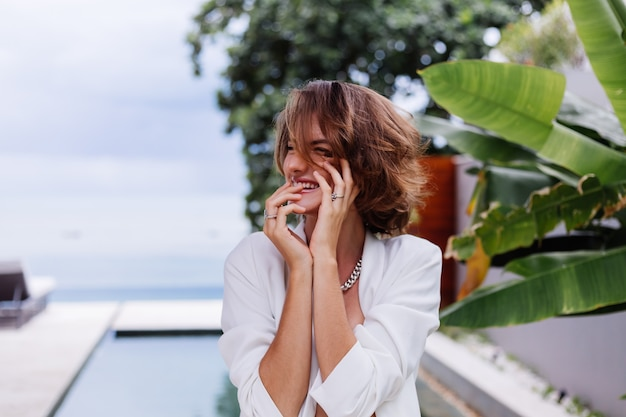 Модный портрет женщины на тропической роскошной вилле в белом стильном пиджаке и украшениях над тропическими листьями