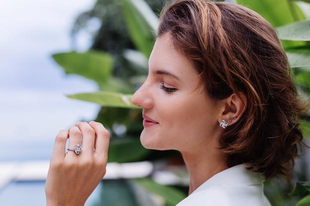 熱帯の葉の上に白いスタイリッシュなブレザーとジュエリーを身に着けている熱帯の高級ヴィラで女性のファッションの肖像画
