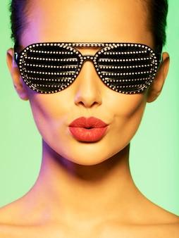 다이아몬드와 검은 선글라스를 착용하는 여자의 패션 초상화. 포화 된 색상