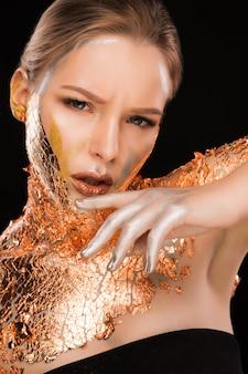 그녀의 얼굴, 목, 어깨에 구리 호일이 있는 멋진 금발 여성의 패션 초상화