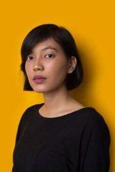 黄色の背景に若いアジアの女性のファッションの肖像画