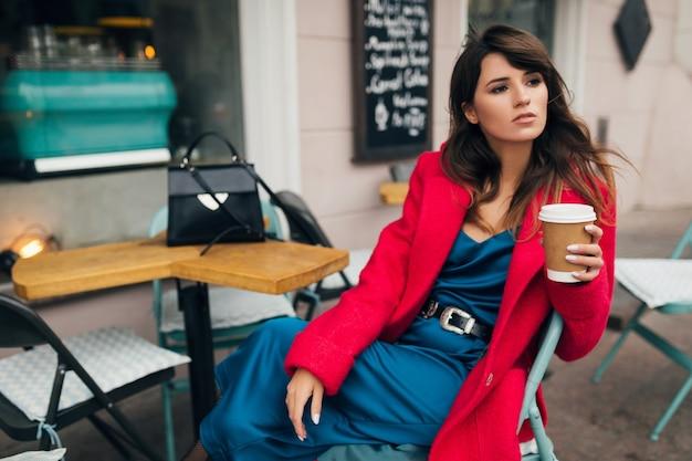 赤いコート、秋のスタイルのトレンド、コーヒーを飲む、青いシルクのドレスを着て、エレガントな女性、楽しみに街のストリートカフェに座っている若い魅力的なスタイリッシュな女性のファッションの肖像画