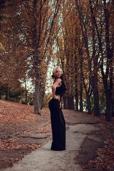 일몰에 오래 된 마을에서 길을 걷고 검은 긴 드레스에서 젊은 아름 다운 여자의 패션 초상화