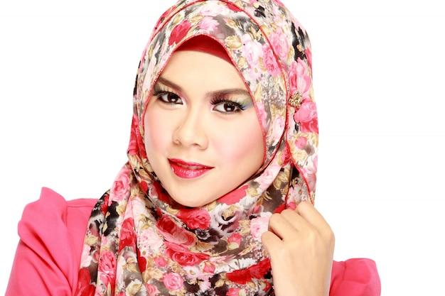 Фасонируйте портрет молодой красивой мусульманской женщины с красным шарфом
