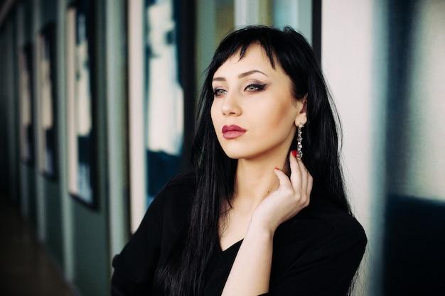 검은 드레스에 젊은 아름 다운 여자의 패션 초상화.