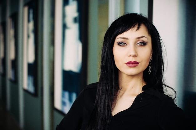 黒のドレスを着た若い美しい女性のファッションの肖像画。