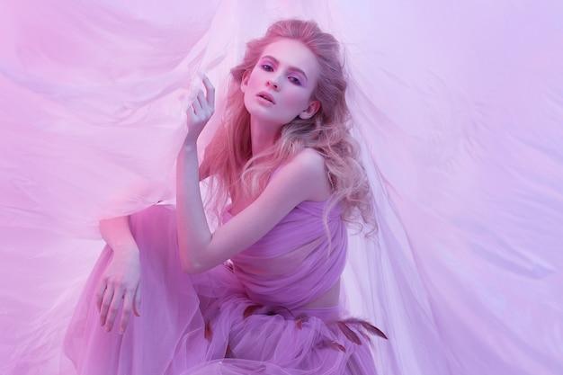 Фасонируйте портрет молодой красивой женщины в пушистом фиолетовом платье. светлые вьющиеся волосы, макияж, платье с перьями, мягкие тона, арт-фото