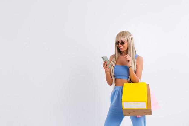 긴 화려한 스트레이트 헤어를 가진 젊은 금발의 여자의 패션 초상화 잡고 다채로운 쇼핑 가방