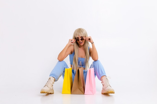 Фасонируйте портрет молодой блондинки с длинными великолепными прямыми волосами с красочными хозяйственными сумками в студии на белом.