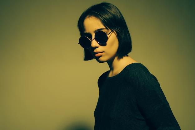 Фасонируйте портрет молодой элегантной женщины в солнечных очках. цветная стена