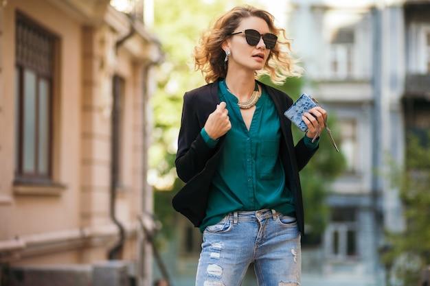 검은 재킷, 녹색 블라우스, 세련된 액세서리, 작은 지갑을 들고 선글라스, 여름 거리 패션 스타일을 입고 거리에서 걷는 젊은 우아한 여자의 패션 초상화