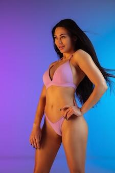 グラデーションの背景に紫色の水着で髪を吹く若いフィット感とスポーティーなブルネットの女性のファッションの肖像画。長髪モデル。夏にぴったりのボディ。美容、リゾート、スポーツのコンセプト。