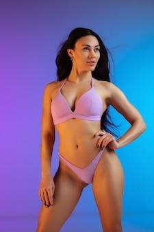 Фасонируйте портрет молодой подходящей и спортивной брюнетки с развевающимися волосами в фиолетовых купальных костюмах на градиентном фоне. длинношерстная модель. идеальное тело, готовое к лету. красота, курорт, спортивная концепция.