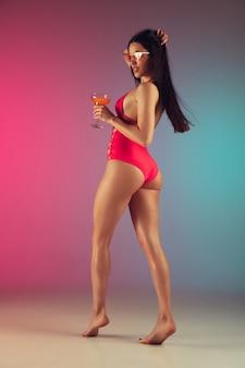 グラデーションの背景にスタイリッシュなピンクの水着で若いフィット感とスポーティーな白人女性のファッションの肖像画。ブルネットの長髪モデル。夏にぴったりのボディ。美容、リゾート、スポーツのコンセプト。