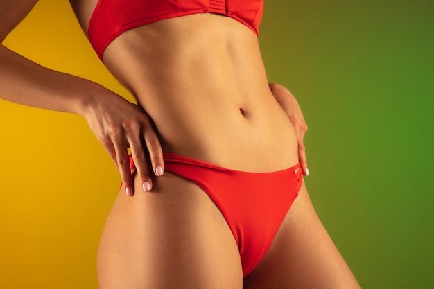 グラデーションの背景にスタイリッシュな赤い水着で若いフィット感とスポーティーな白人女性のファッションの肖像画。お腹と足をフィットさせます。夏にぴったりのボディ。美容、リゾート、スポーツのコンセプト。