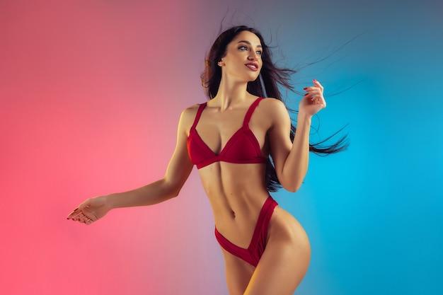 Модный портрет молодой подтянутой и спортивной женщины в стильных красных роскошных купальниках на градиентной стене с идеальным телом, готовым к лету