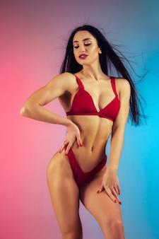 夏の準備ができてグラデーションの壁の完璧なボディにスタイリッシュな赤い豪華な水着で若いフィット感とスポーツの女性のファッションの肖像画